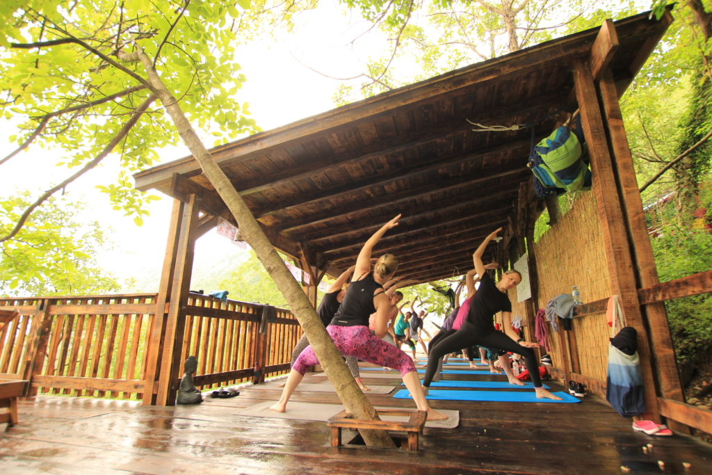 People on a yoga holiday in Montenegro participating in a yoga workshop outside on a wooden deck at Villa Miela near Lake Skadar