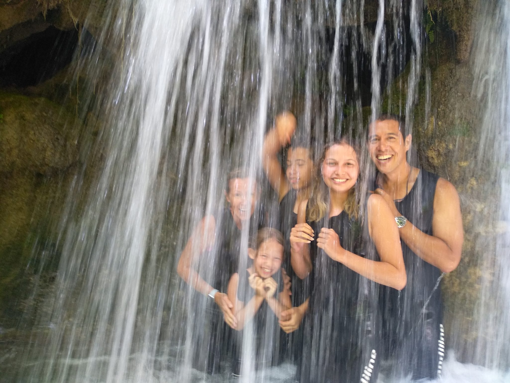 Happy family laughing as they walk through an isolated waterfall we have found on our guided tours.