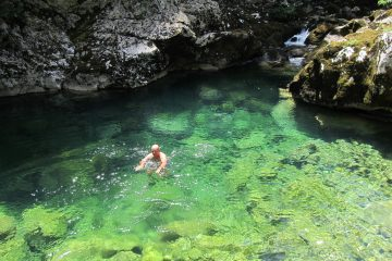 Man on an activity holiday swimming in a crystal clear, bright blue rock pool near Lake Skadar