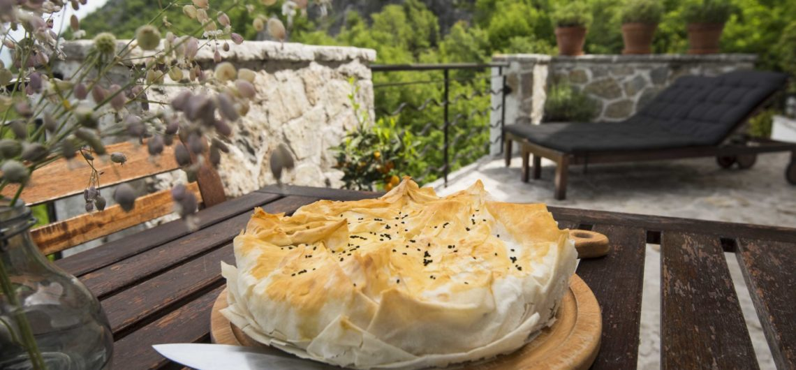 A freshly baked filo pastry pie stuffed with wild greens which Montenegrins call Zelena Pita, placed on the outdoor table of Villa Miela's terrace with a backdrop of rocky mountains at Lake Skadar National Park