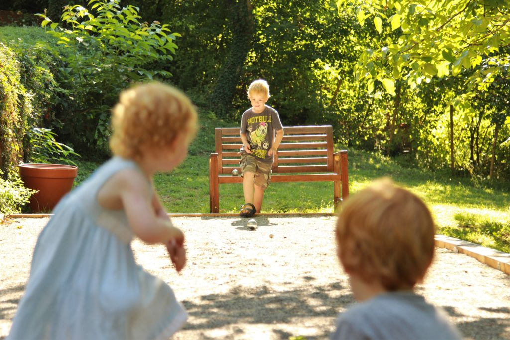 kids playing boules on a homemade boules court