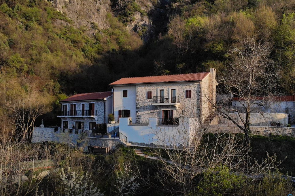 Two stone villas in Montenegro on a steep hillside surrounded by rock and forest