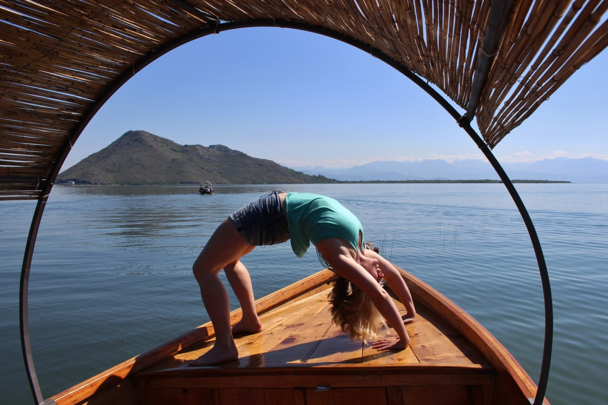A woman on a yoga holiday in Montenegro doing a wheel pose while on a boat tour at Lake Skadar National Park on a warm sunny day